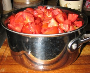 Pot overflowing with tomatoes.